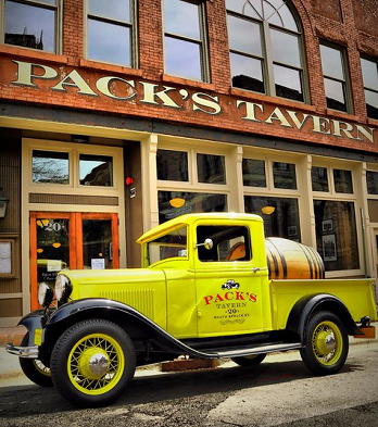 Pack's Tavern with a vintage yellow truck parked out front.