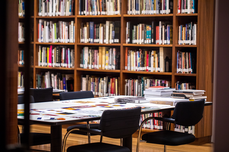 Table in a library with books in the background.